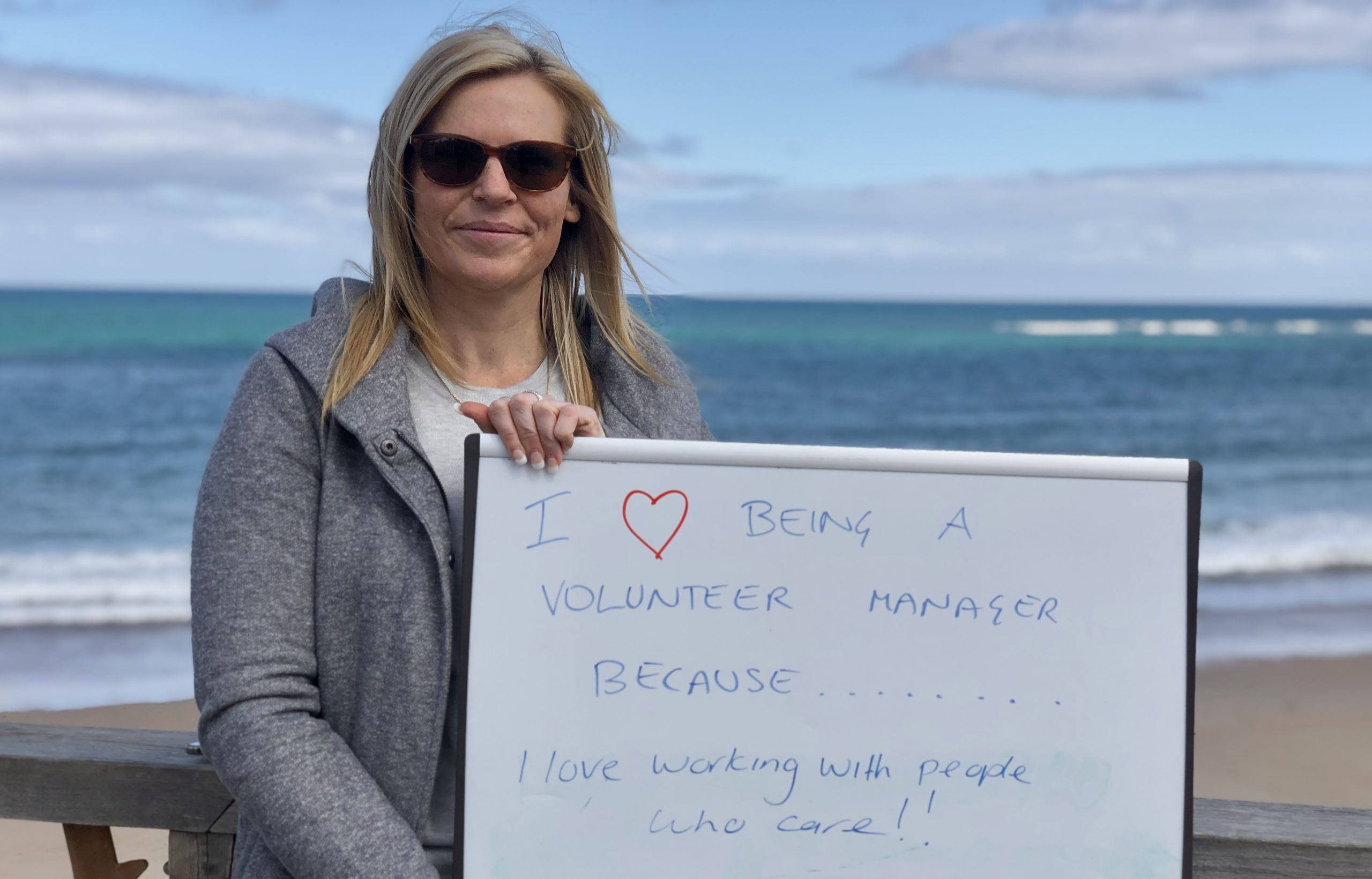 """A woman holds up a sign that reads """"I love being a volunteer manager because I love working with people who care""""."""