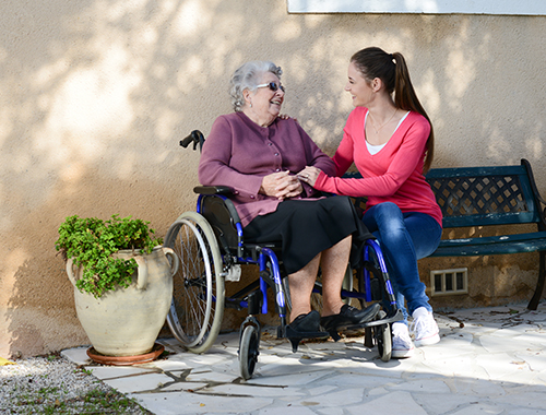 A female volunteer visits with an older woman in a wheelchair