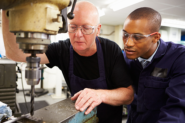 Southern suburbs volunteer over 50 teaches a young man to use a milling machine
